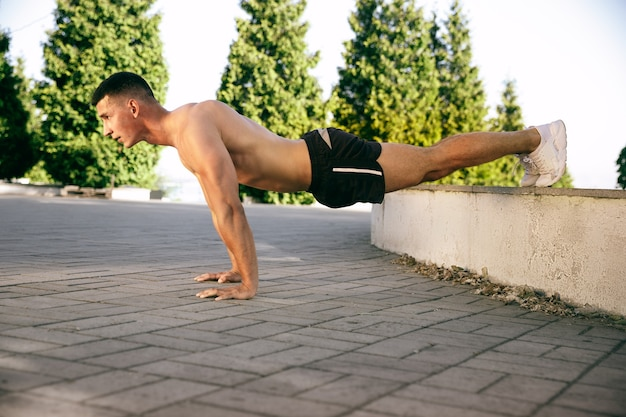 A muscular male athlete doing workout at the park. gymnastics, training, fitness workout flexibility. summer city in sunny day on background field. active and healthy lifestyle, youth, bodybuilding.