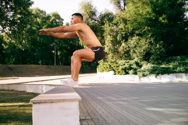 Un atleta maschio muscoloso che fa allenamento al parco. ginnastica, allenamento, flessibilità allenamento fitness. città estiva in una giornata di sole sul campo spaziale