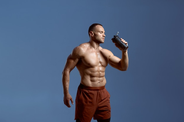 Muscular male athlete drinks water from sports bottle, photo shoot in studio, blue background. one man with athletic build, shirtless sportsman in sportswear, active healthy lifestyle