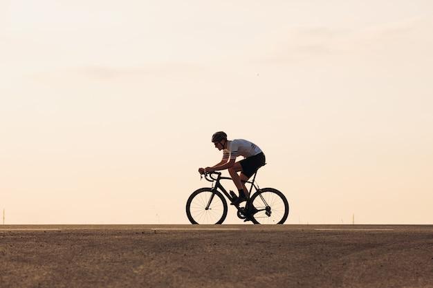 일몰 동안 아스팔트 도로에서 자전거 타기 및 보호용 헬멧에 근육질의 남성 운동 선수