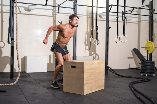 Muscular male athlete is practicing jumping on a wooden box in modern health club functional training