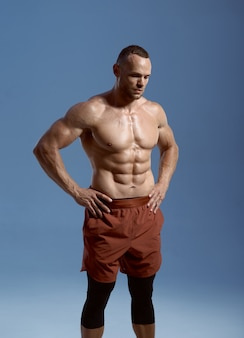 Muscular male athlete, photo shoot in studio, blue background. one man with athletic build, shirtless sportsman in sportswear, active healthy lifestyle