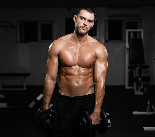 Muscular male athlete posing with dumbbells in the gym