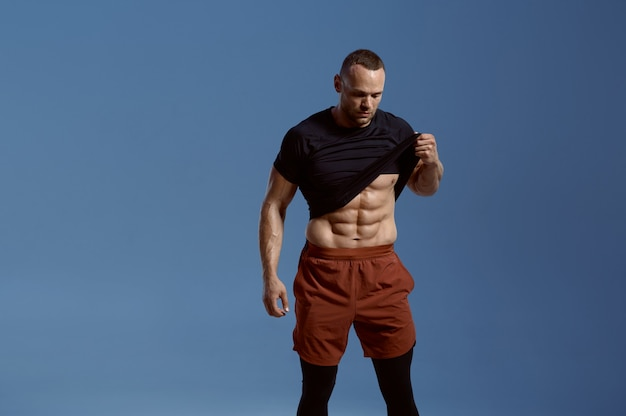 Muscular male athlete shows his abs in studio