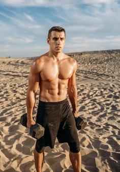 Мускулистый спортсмен-мужчина с гантелями в пустыне