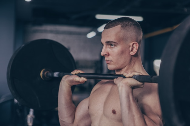 Muscular male athlete working out with barbell at gym studio