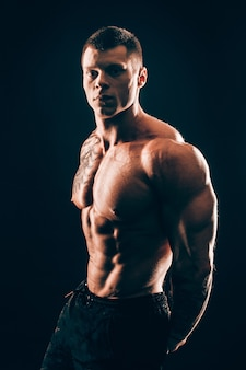 Muscular male bodybuilder looking at the camera.isolated on black background