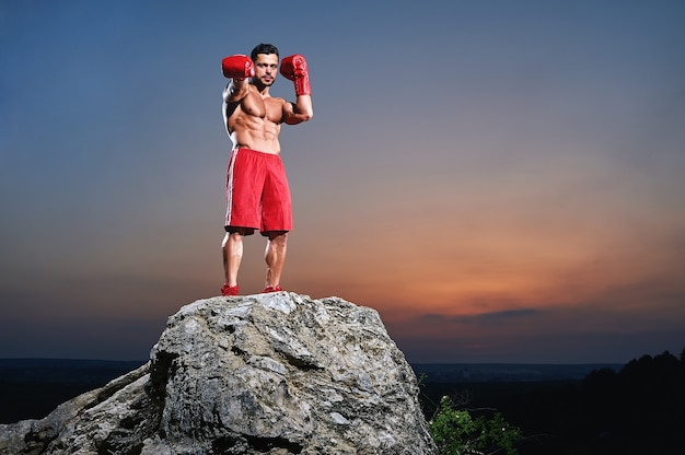 Muscular male boxer looking at camera outdoors