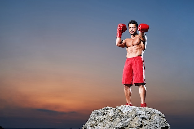 Muscular male boxer posing and looking at camera outdoors