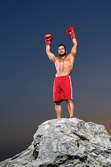 Muscular male boxer posing outdoors