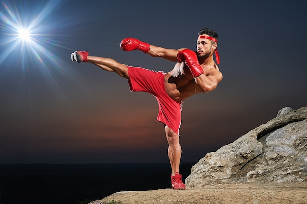 Мускулистый боксер тренируется на открытом воздухе