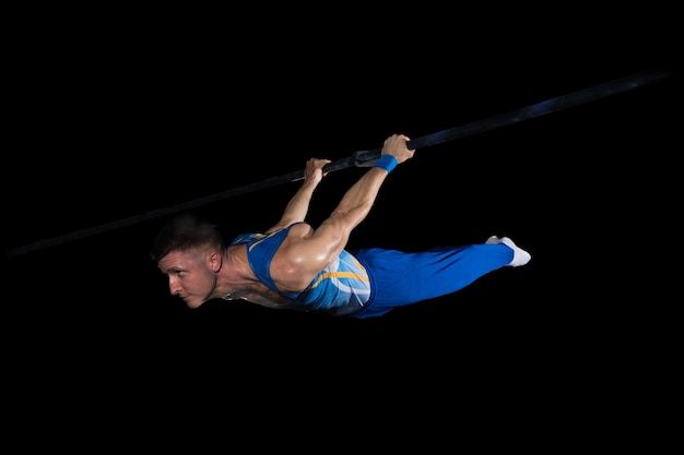 青のジムの柔軟でアクティブな白人のフィット男アスリートでの筋肉の男性体操選手のトレーニング