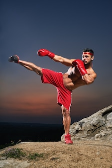 Muscular male kickboxer training outdoors