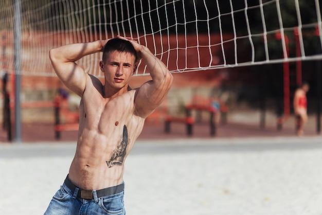 ブルージーンズでポーズをとって完璧なボディを持つ筋肉の男性モデル
