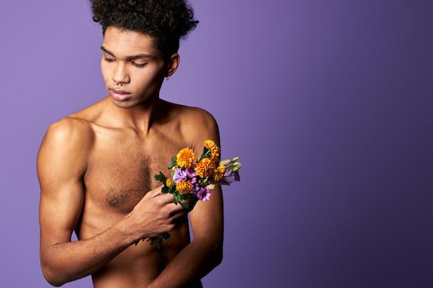 紫色の背景の肖像画に花の花束を持つ筋肉の男性は、運動ヒスパニック系の若い男を撮影しました