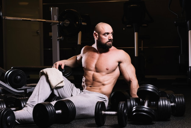 Muscular man amidst dumbbells
