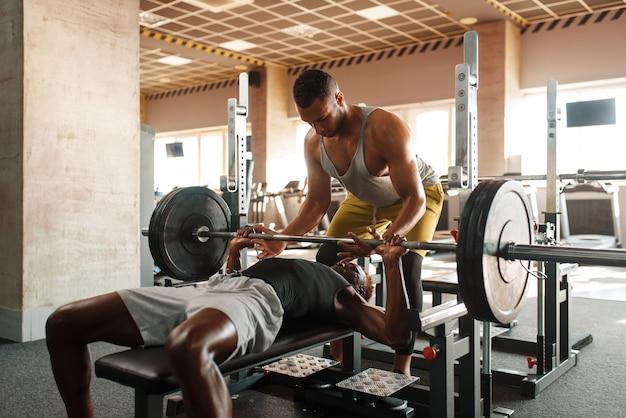 筋肉男と彼のトレーナーは、ジムでトレーニングのバーベルで運動をしています。