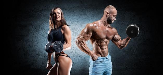 Мускулистый мужчина и женщина позирует с гантелями на темном фоне. бодибилдинг и фитнес-концепция. смешанная техника
