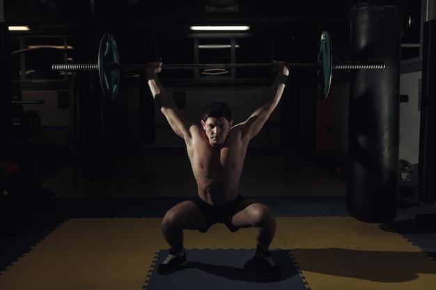 바벨을 드는 크로스핏 체육관에서 근육질의 남자.