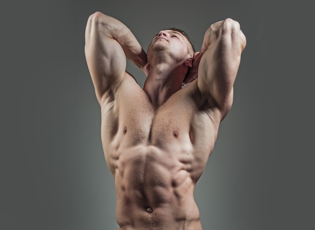 벌거 벗은 몸통과 회색 스튜디오에서 6 팩 또는 복근이있는 강한 배가있는 섹시한 근육질 운동 몸매를 가진 근육질 남자 선수 보디 빌더