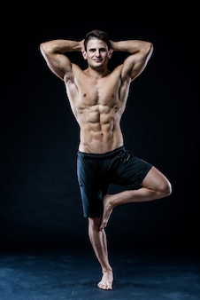Muscular man balancing on the one leg feeling relaxed