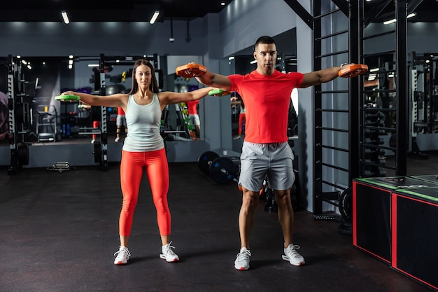 A muscular man and a beautiful young woman doing some arm and shoulder exercises together in the indoor gym at night time