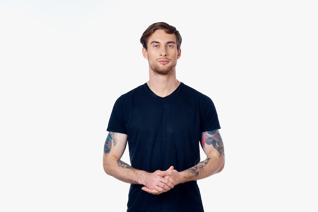 Muscular man in a blue tshirt with tattoos on his arms on a light background cropped view