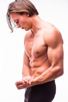 白い壁に分離された6パックの筋肉の男の体