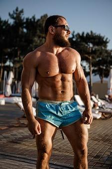 Muscular man bodybuilder tanning in a beach club