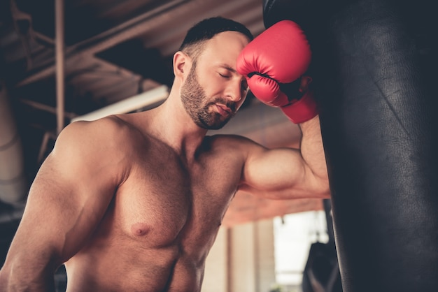 Muscular man in boxing gloves is practicing.