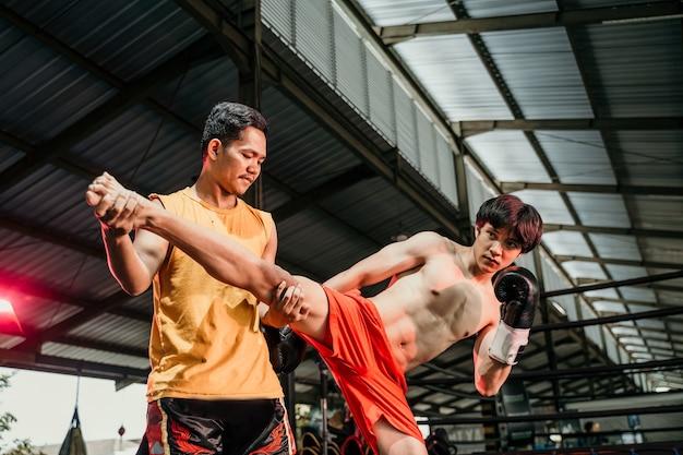 권투 링에 발로 운동을 하 고 그녀의 트레이너와 장갑에 권투 근육 남자. 코치와 함께 남자 복서 훈련