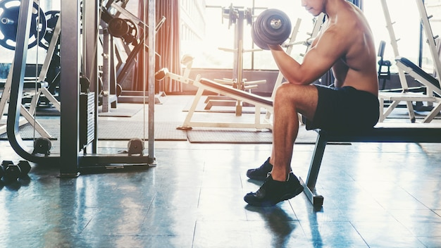 Muscular man built athlete working out in gym sitting on weightlifting machine