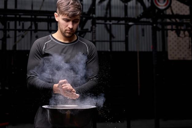 タルクで手をたたき、ジムでのトレーニングの準備をしている筋肉質の男。チョーク炭酸マグネシウムでジムでフィットトレーニングの準備をしている運動白人男性の手