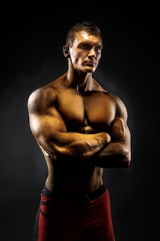 Muscular man crossed his arms. black background