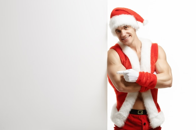 Muscular man disguised as santa leaning against a white sign