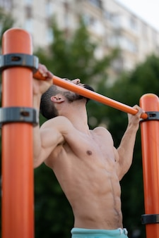 A muscular man does pull ups on a horizontal bar on the street on a sports field