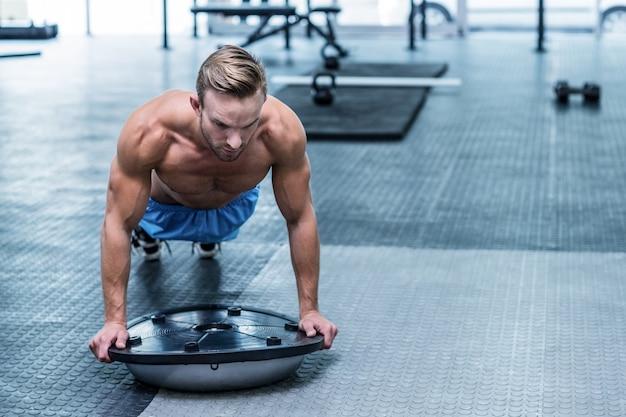Muscular man doing bosu ball exercises