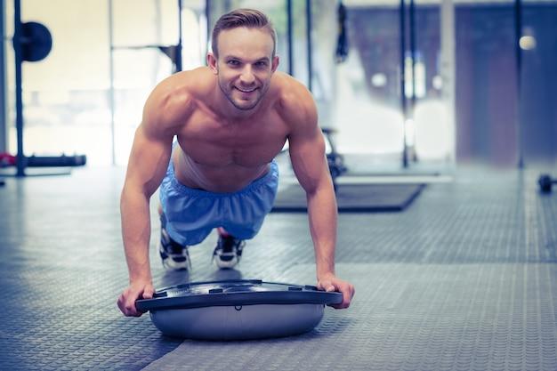 Мускулистый человек делает упражнения на босу
