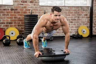 Muscular man doing bosu push ups