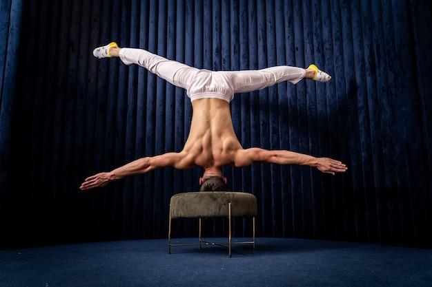Мускулистый мужчина делает упражнения дома концепция индивидуальности, творчества и здорового образа жизни