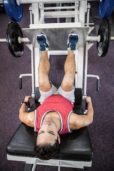 Muscular man doing exercise for legs in the gym