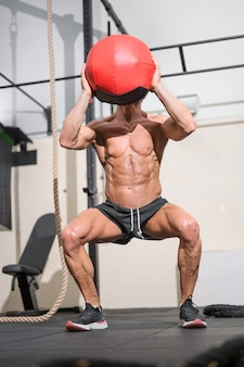 Muscular man doing exercise with medicine ball in gym