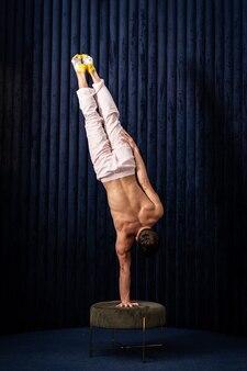 Мускулистый мужчина делает стойку на руках одной рукой дома концепция творчества йоги и здорового образа жизни