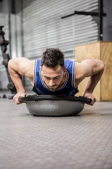 Muscular man doing push up on bosu ball at the crossfit gym