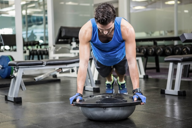 Muscular man doing push up with bosu ball at the gym