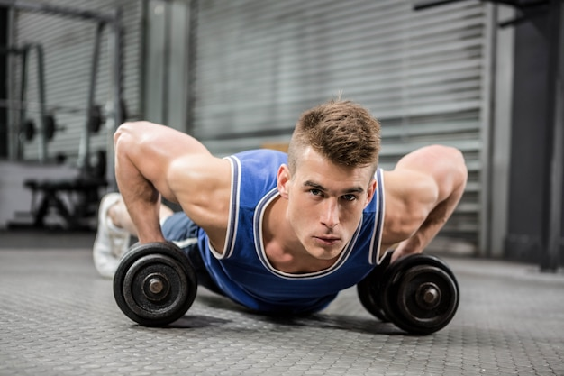 Muscular man doing push up with dumbbells at the crossfit gym