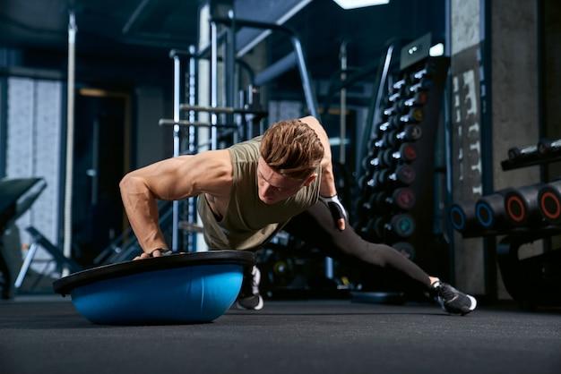 밀어 넣기를 수행하는 근육 남자는 한 손에 올립니다.