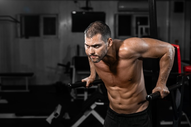Muscular man doing push-ups on uneven bars in crossfit gym.