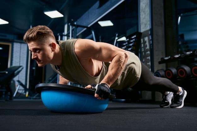 Мускулистый мужчина делает отжимания, используя баланс мяч.