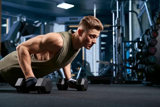 Мускулистый мужчина делает отжимания с помощью гантелей.